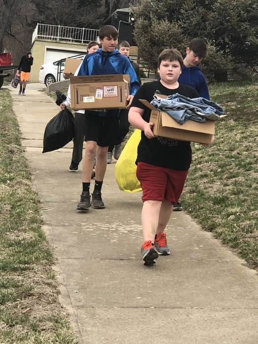 8th grade carry donations for flood relief.