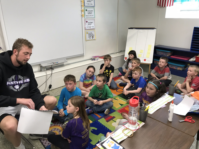 Noah reading his children's book he wrote and illustrated to the first grade class.